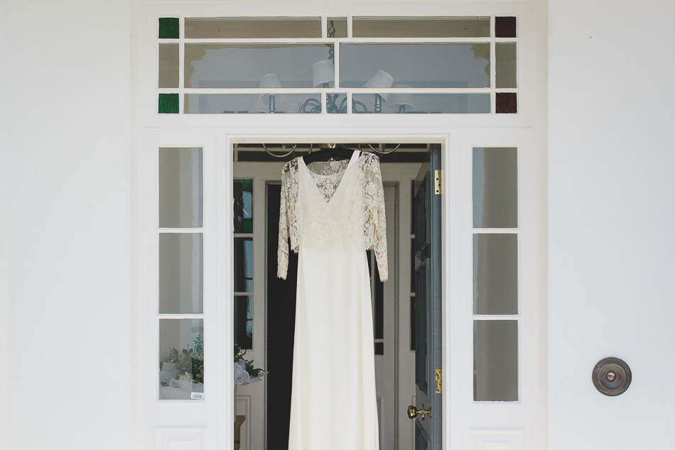The Brides dress hanging in a doorway at a wedding in Jersey, Channel Islands