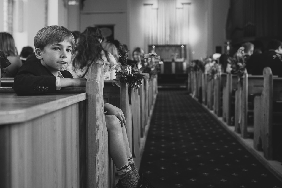 Boy looking at the camera in church at a wedding in Jersey, Channel Islands