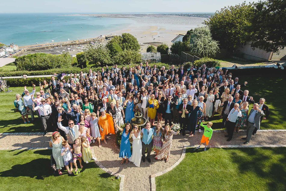 Group photo of wedding guests overlooking Gorey at a wedding in Jersey, Channel Islands