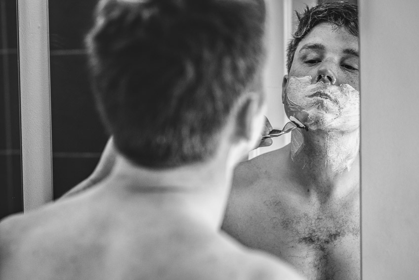 Groom reflection mirror while shaving