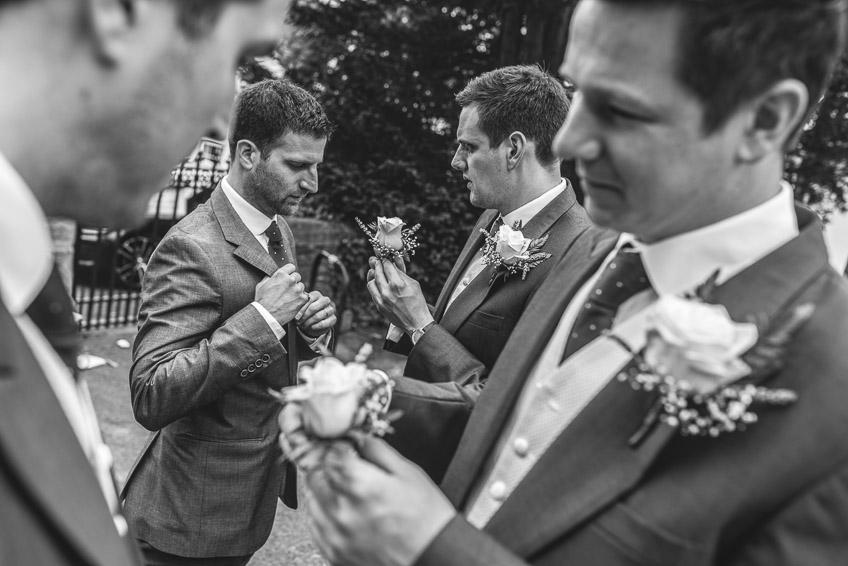groomsmen pinning their buttonhole flowers