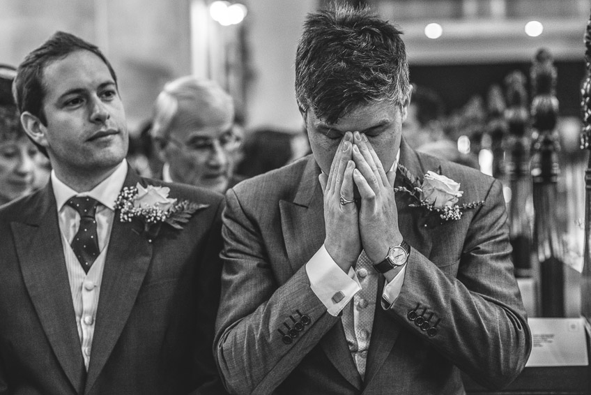groom holding hands to face during ceremony