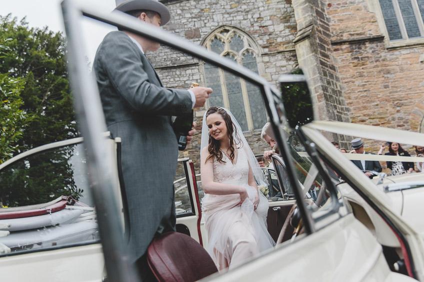 bride stepping into wedding car