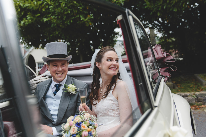 bride and groom smiling in car