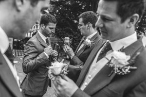 groomsmen pinning their buttonhole flowers