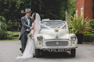 portait of bride and groom next to car