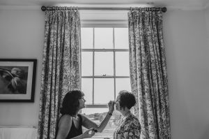 Bride having make up applied in the window